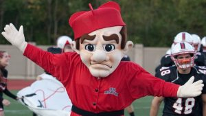 The OWU Bishop mascot, running on a field with football players in the background